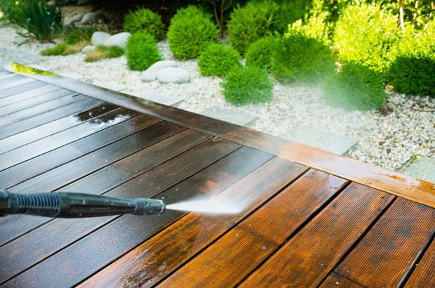high pressure water cleaning a wooden deck