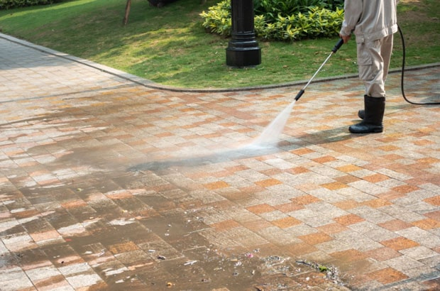 person cleaning a park pathway with a high pressure cleaner