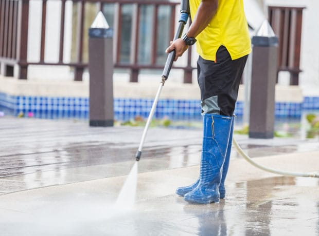 man using high pressure water cleaner on walkway ourside business