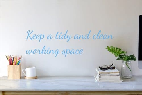 """clean marble-top desk with pencils, a cup, a stack of books with reading glasses on them and a fern in a mason jar, with the caption """"Keep a tidy and clean working space"""""""