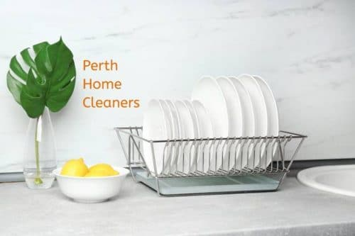a wire rack of clean, white plates on a white marble counter top next to a white bowl of three lemons and a clear vase with two large leaves. The words Perth Home Cleaners are on the white marbled wall.