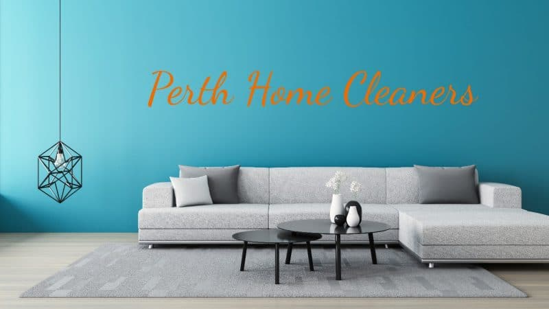 a grey couch set with two black coffee tables on a grey rug, which is on top of a light-coloured wooden floor. The back wall is blue. The words Perth Home Cleaners are in orange on the wall. A fancy, wrought-iron chandelier in the shape of a cut diamond is hanging down almost touching the ground