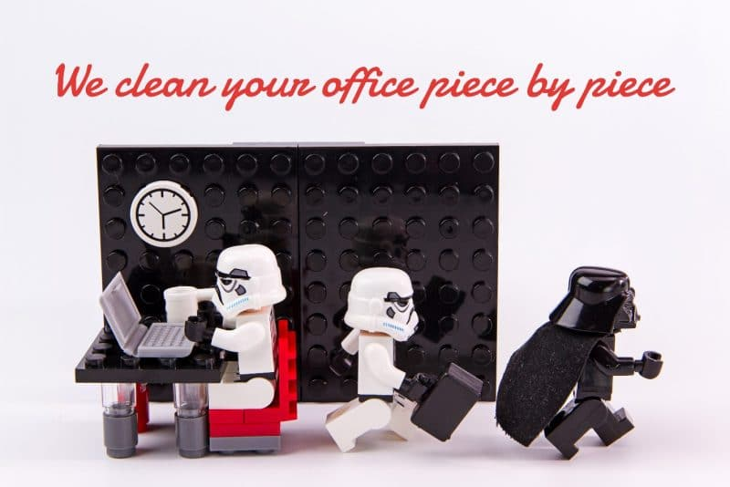 starwars lego scene. A stormtrooper is sitting on a red chair, typing on a grey laptop with a white coffee mug next to him and a clock above him. Another stormtrooper is walking away from the first, carrying a black briefcase and following darth vader, who is walking in the same direction. The words we clean your office piece by piece.