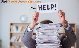 man in a grey suit, hiding behind a stack of paperwork so only his arms and the top of his head is visible. The caption reads ask Perth Home Cleaners for help. The word help is on a piece of paper held up by the man in the suit