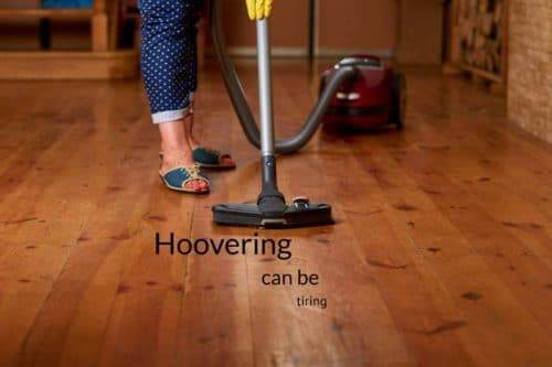 person in blue pants and green sandals vacuuming hardwood floor with words hoovering can be tiring