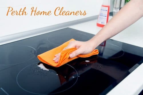 A woman's arm and hand is visible. She is using an orange cloth to wipe down a black glass electric stovetop. A bottle of red cleaning fluid is in the background. The caption reads Perth Home Cleaners